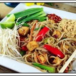 close up view of vegan pad thai on a white plate.
