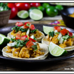 Side view of jackfruit tacos with lime and tomato in the background.