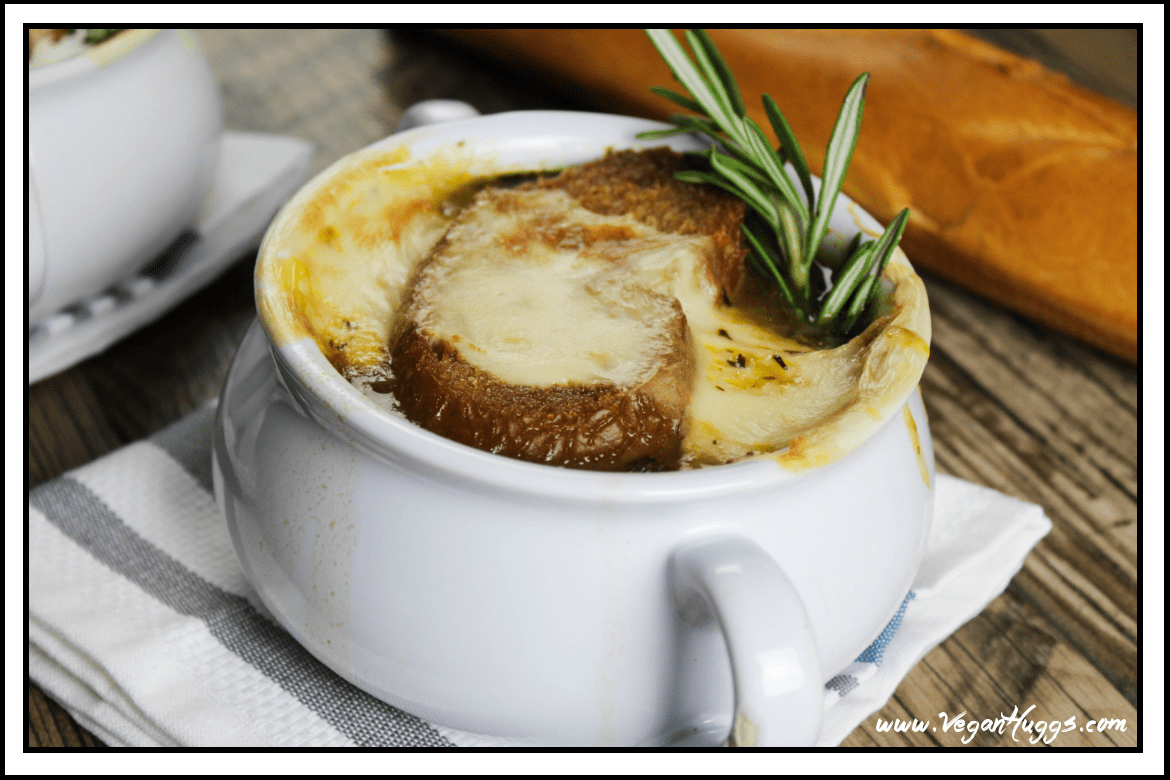 Side view of vegan french onion soup in a white crock on top of a striped napkin. Rosemary sticking out.