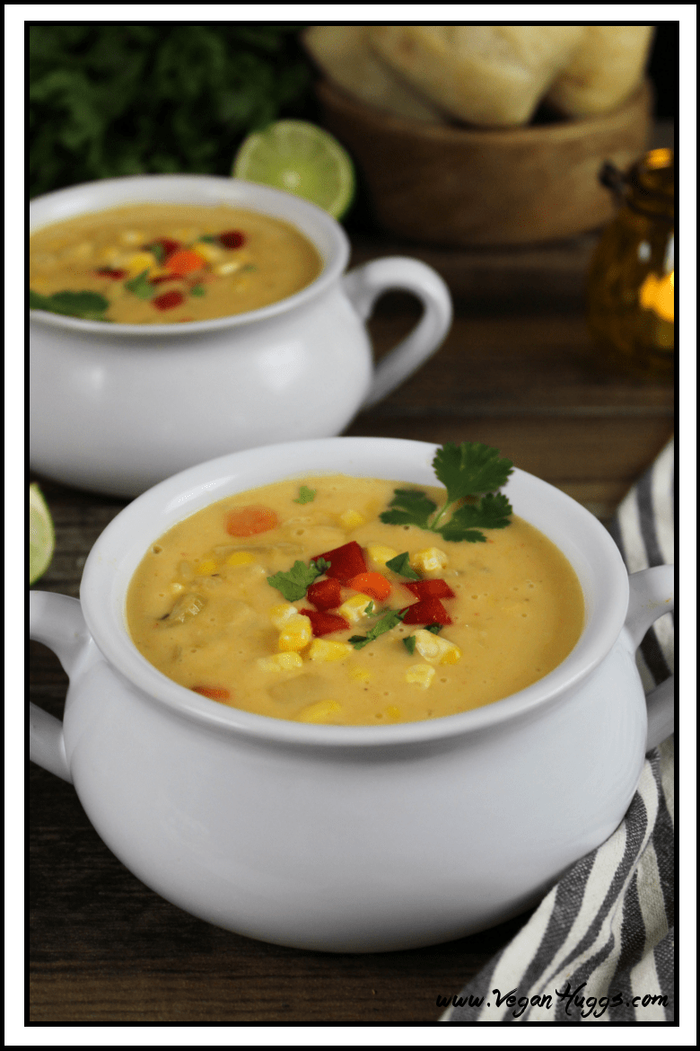 Two bowls of potato corn chowder with bread in the background.