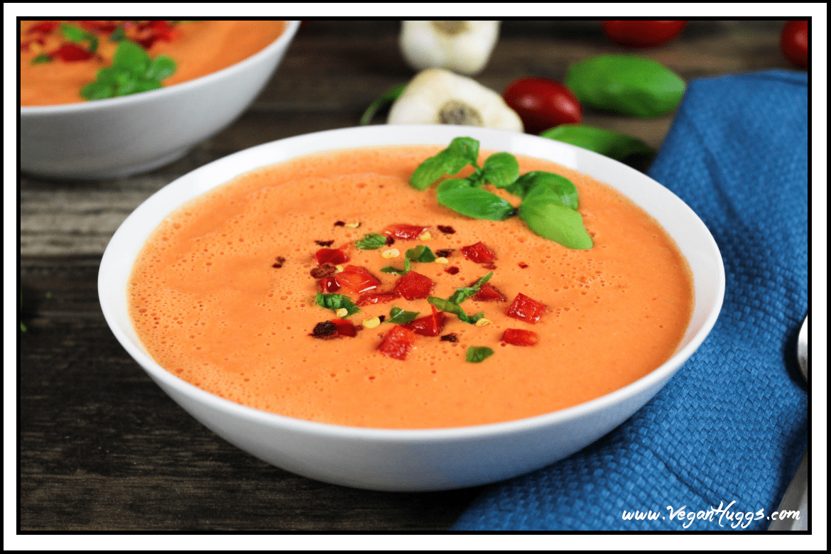 White bowl filled with tomato soup. Topped with fresh basil and red chili flakes.