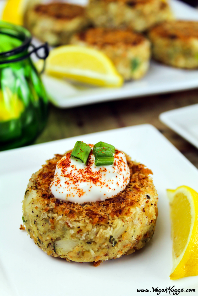 Vegan Crab Cakes on a white plate. Topped with tartar sauce and green onion.