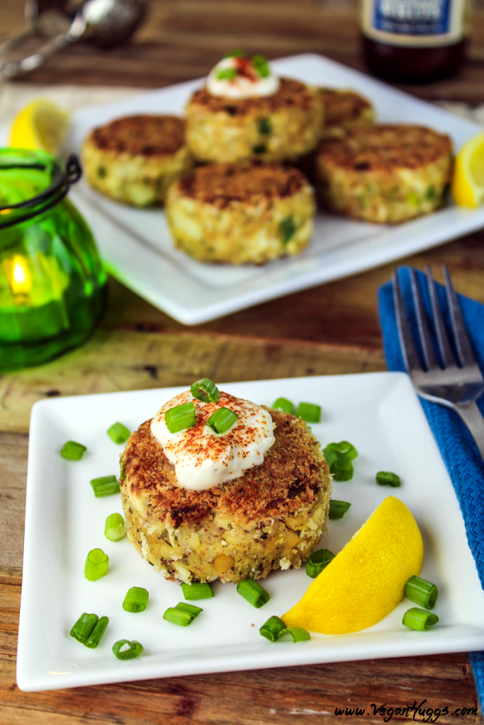 Vegan crab cakes on two serving plates. Green candle in the background with beer.