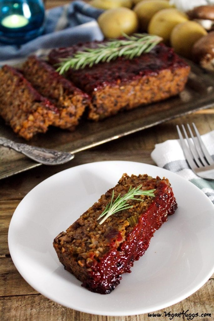 One piece of vegan meatloaf on a white plate. Striped napkin and fork on the side.