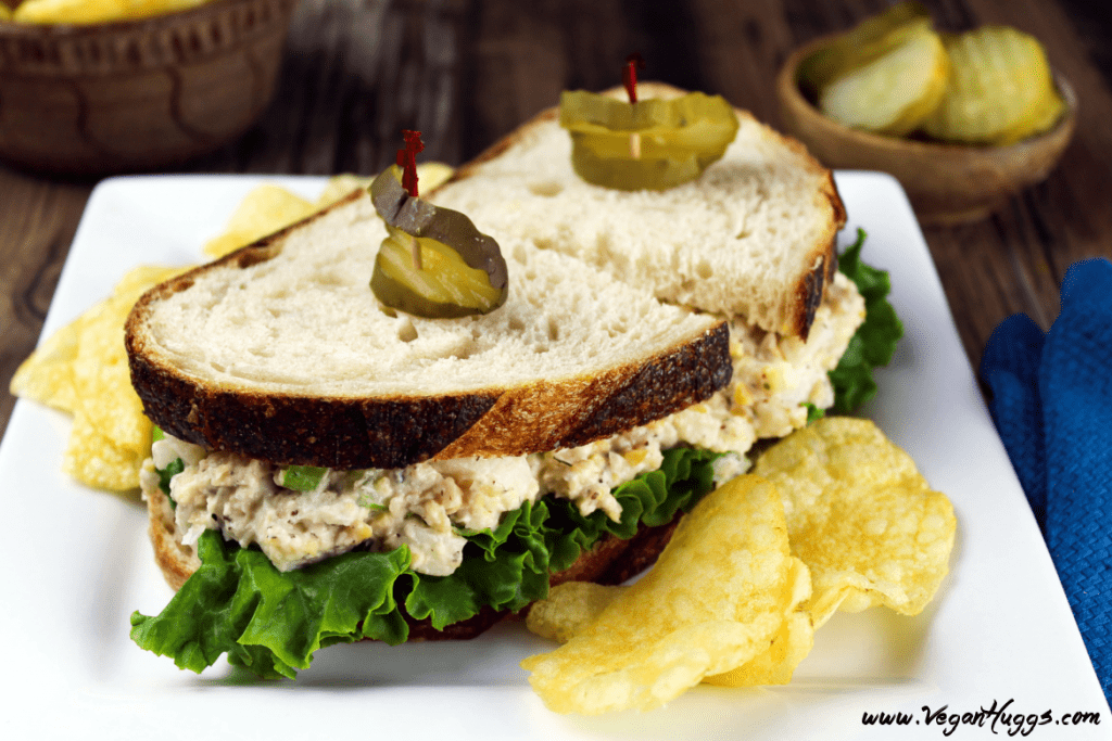 vegan tuna sandwich on a white plate with chips on the side and topped with pickle slices.