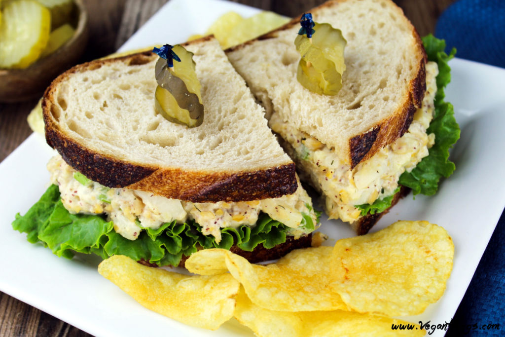 closeup view of Vegan Tuna Salad Sandwich on a white plate. Chips and pickles on the side.