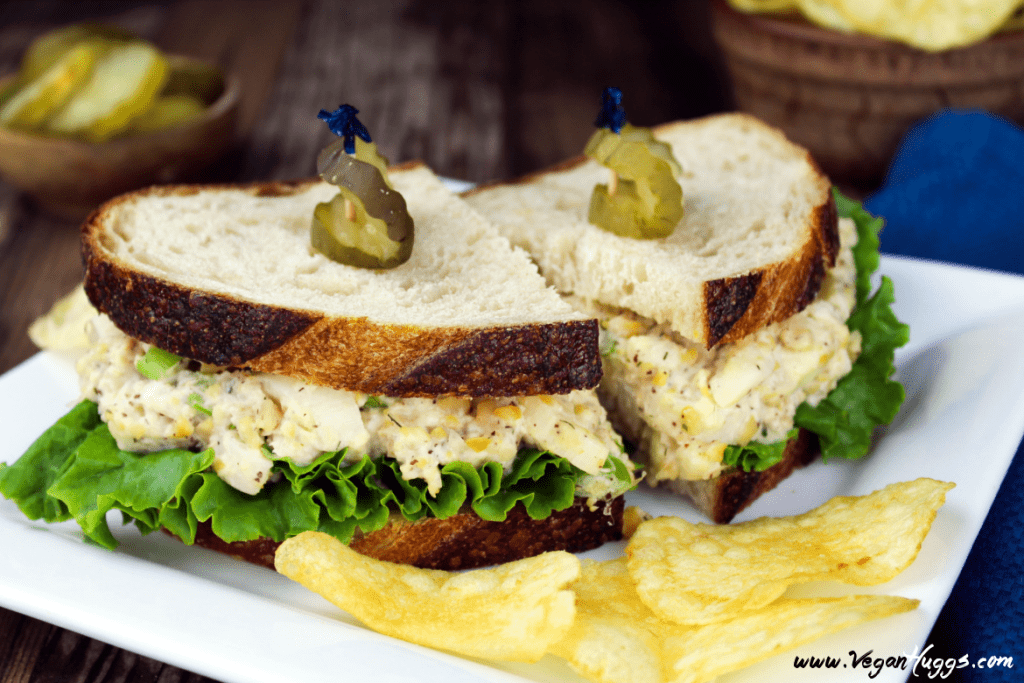 Vegan Tuna Salad Sandwich on a white plate with chips on the side.