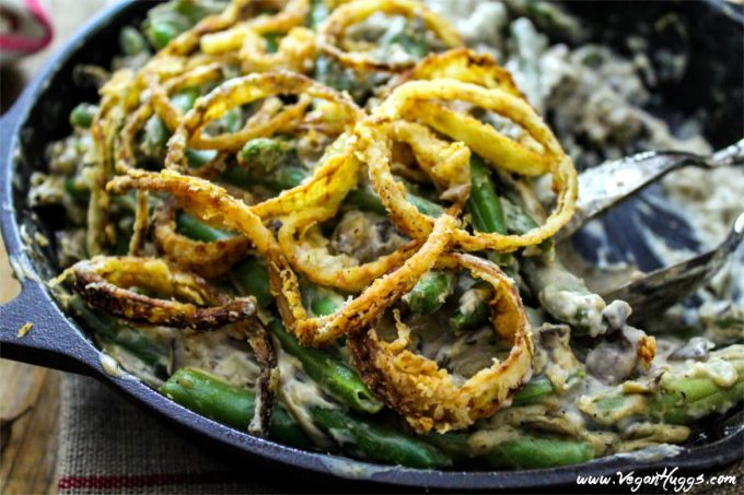 Vegan Green Bean Casserole in a cast iron skillet with silver serving spoon inside.