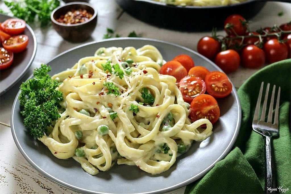 vegan fettuccine alfredo on a gray plate with a side of tomatoes and parsley.