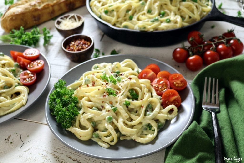 Two plates of cooked pasta with a skillet of pasta in the background.