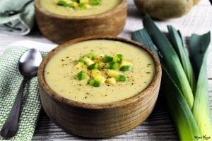 Horizontal photo of two bowls of vegan potato leek soup.