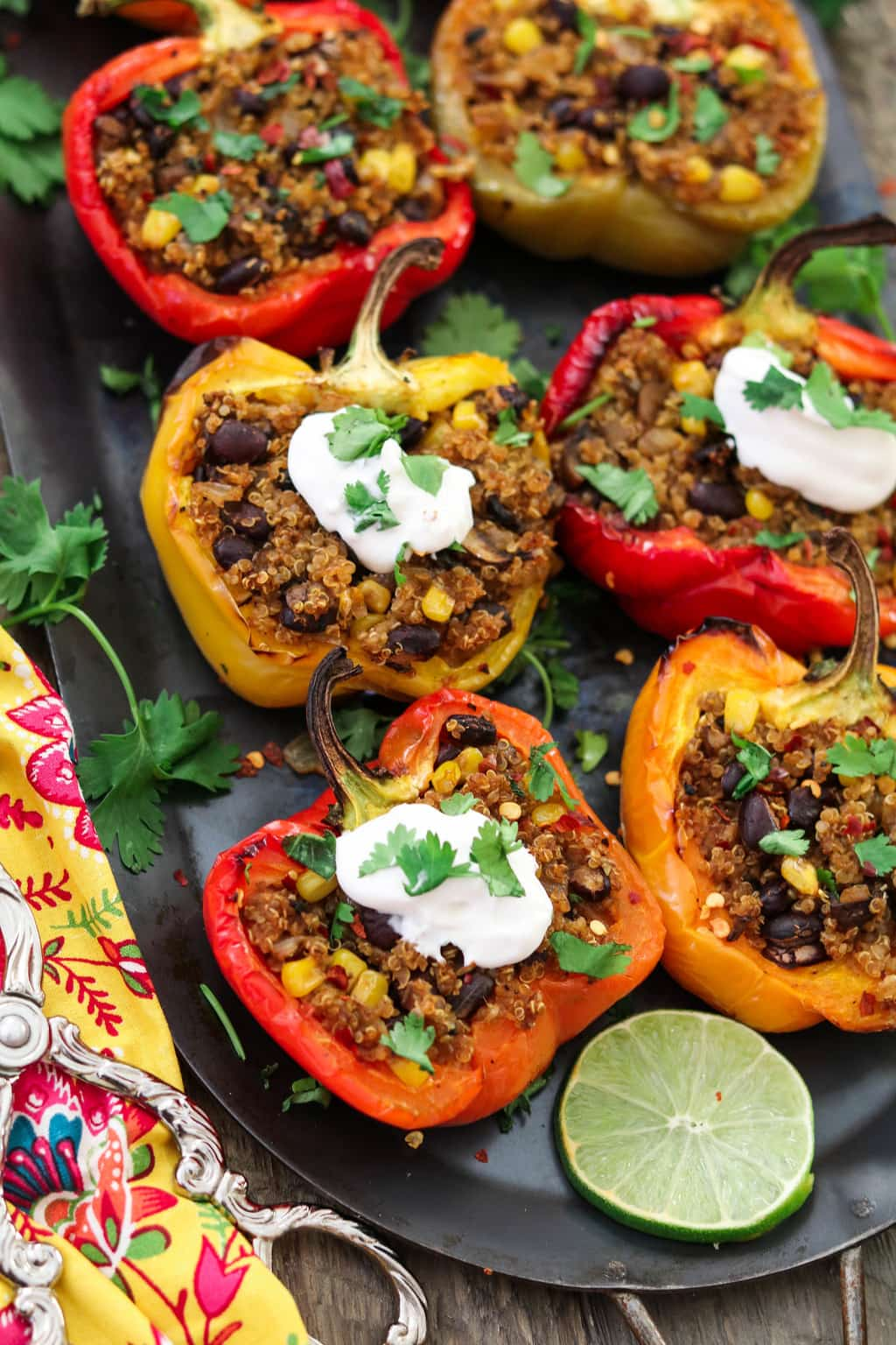Closeup vertical photo of 6 quinoa stuffed peppers. Side of lime and cilantro.