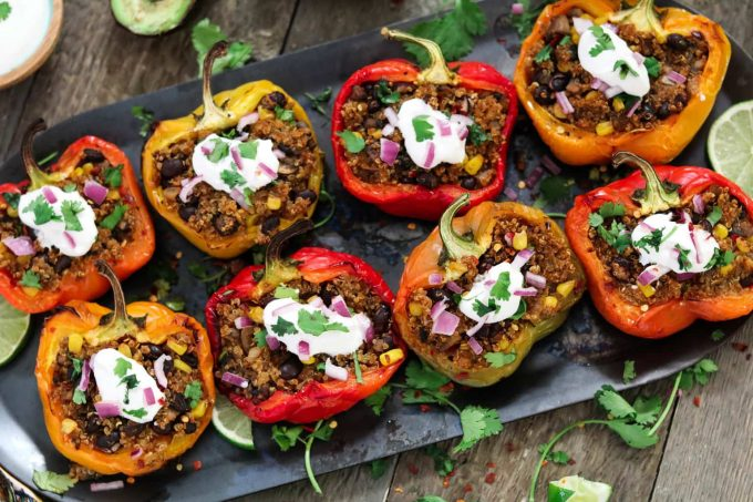 8 quinoa stuffed peppers diagonally on a pan. Fully loaded with sour cream, red onion and cilantro.