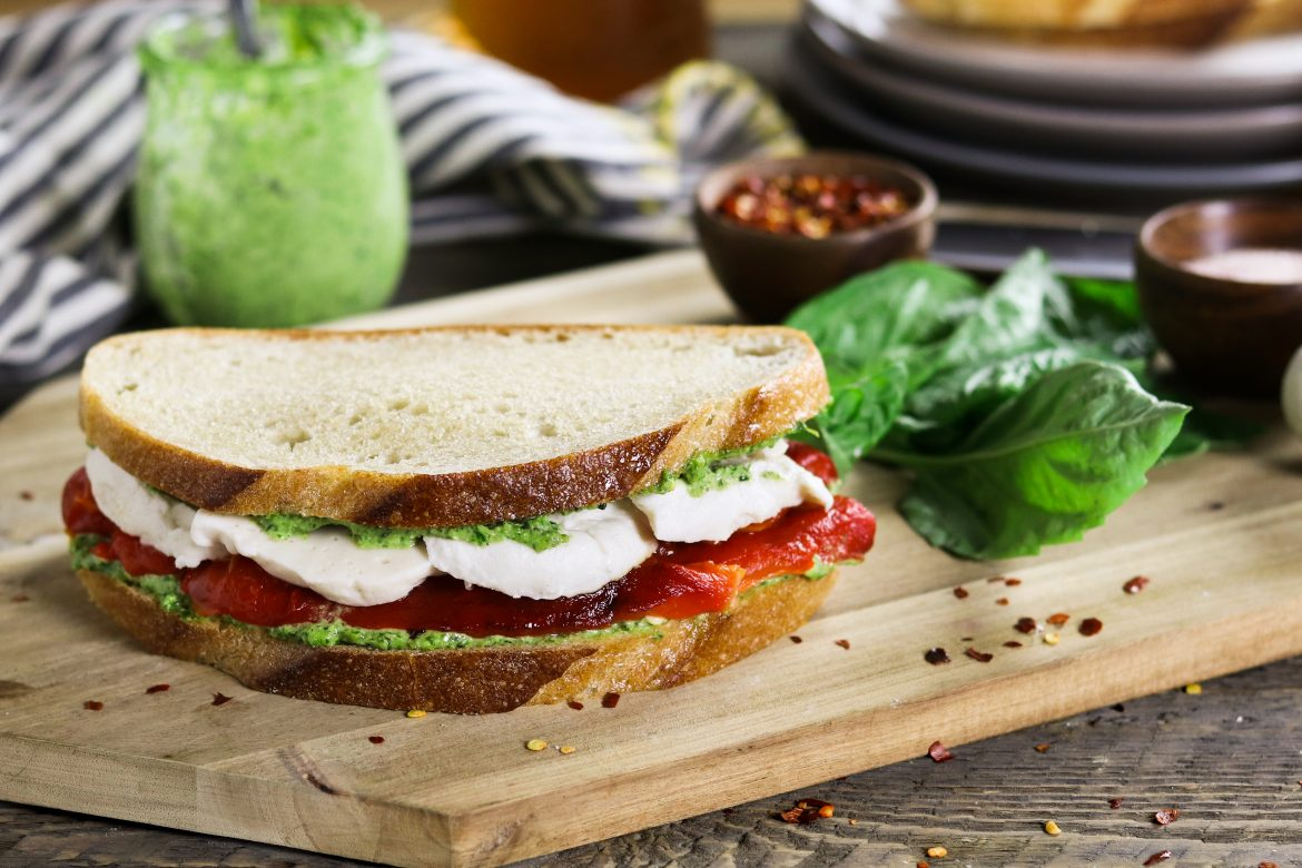 This Roasted Red Pepper Sandwich is built with three layers of deliciousness...creamy vegan mozzarella, cheesy pesto & smoky-sweet peppers.
