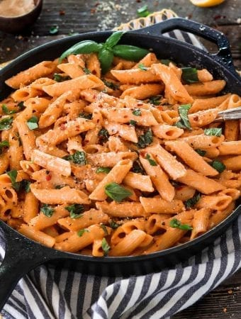 A cast iron skillet filled with roasted red pepper pasta topped with fresh basil.