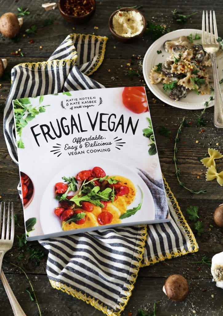 Frugal vegan cookbook on a striped napkin. Plate of vegan mushroom stroganoff on the side.