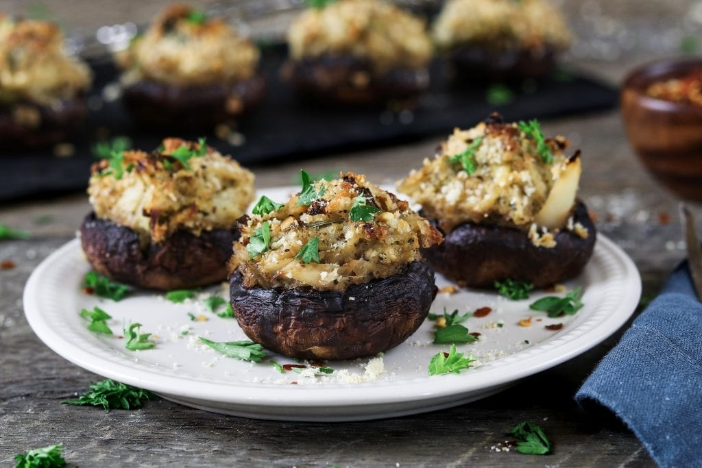 3 Vegan Stuffed Mushrooms on a white plate and topped with fresh parsley.