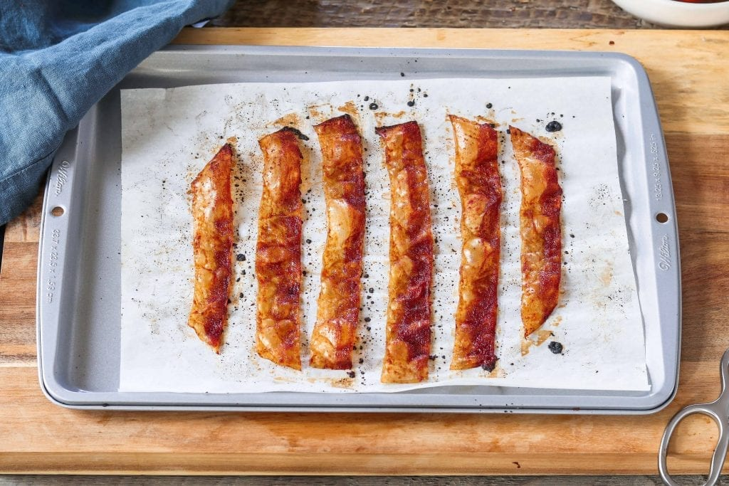 Fully cooked rice paper vegan bacon strips on a baking tray.