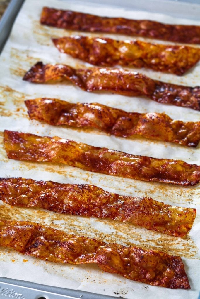 Vertical photo of cooked rice paper vegan bacon on a baking sheet