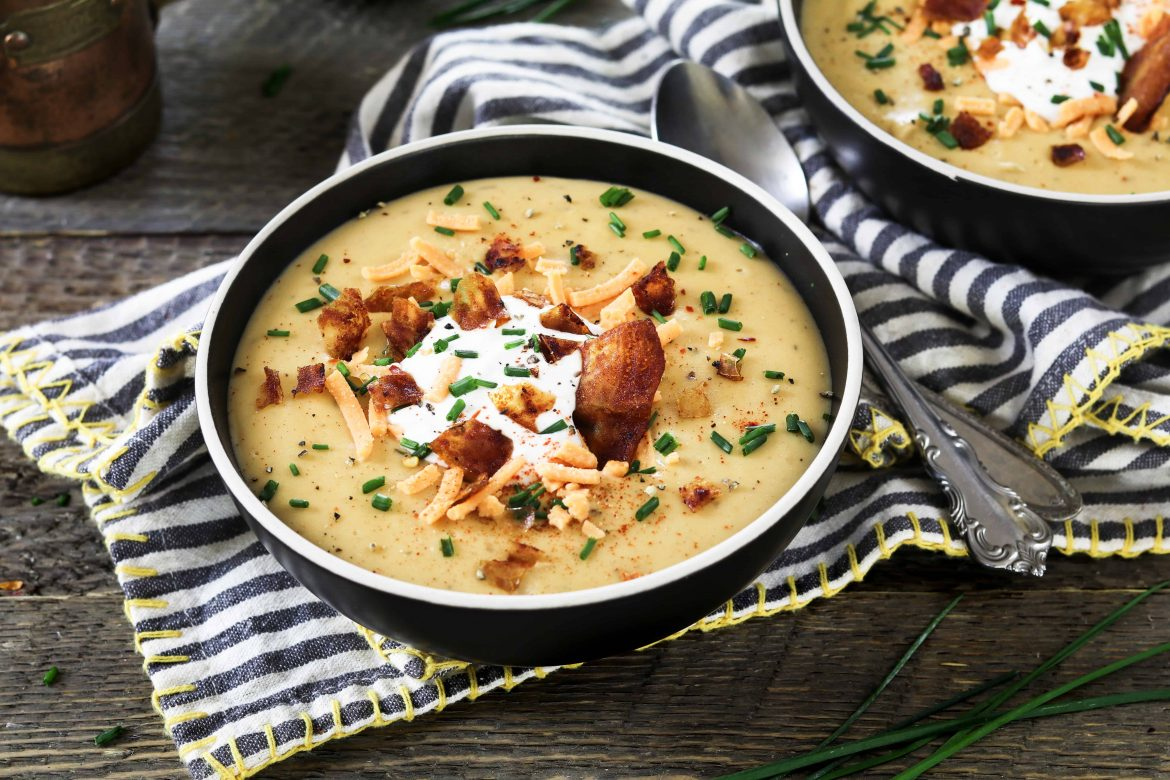 Horizontal photo of two bowls of vegan baked potato soup