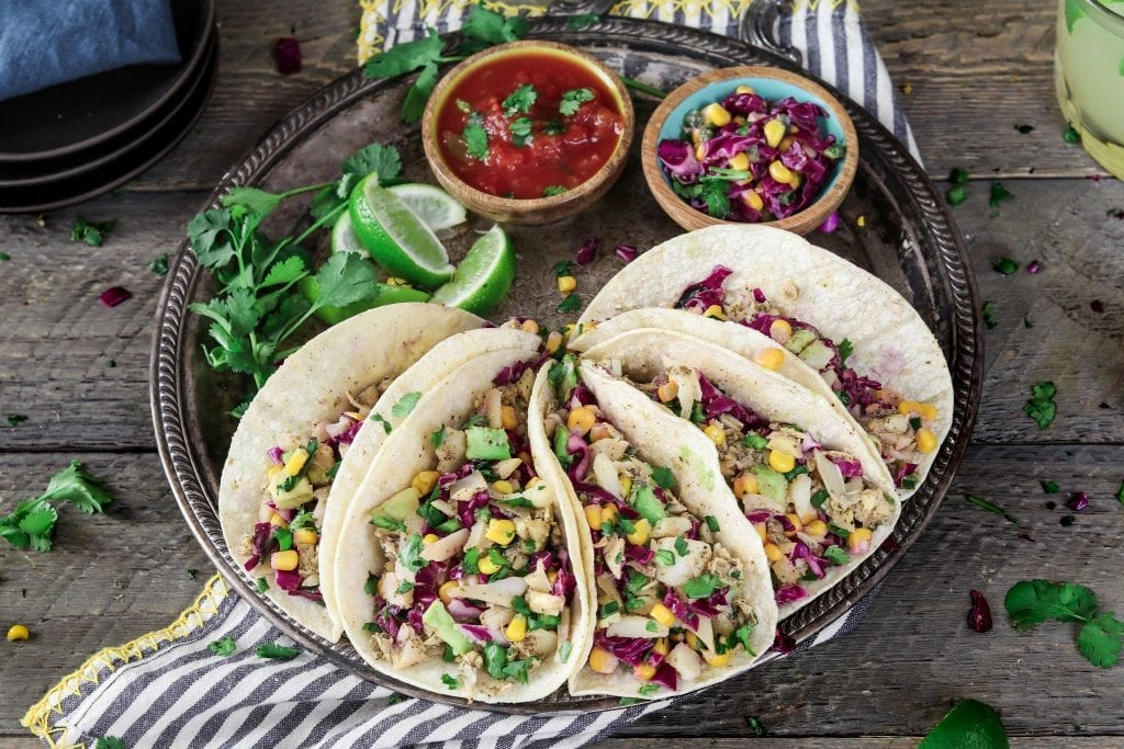 Overhead photo of five vegan fish tacos on a tray. Salsa, corn slaw and lime on the side.