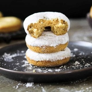 3 Vegan Powdered Donuts stacked on each other on a grey plate.