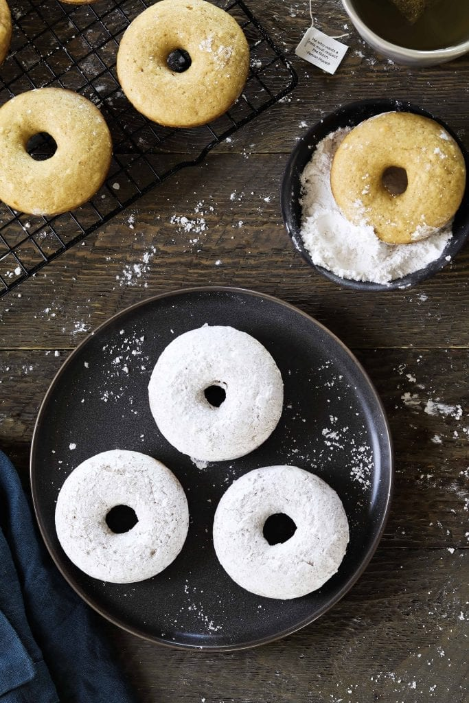 3 vegan powdered donuts on a grey plate and 3 plain donuts about to be coated.
