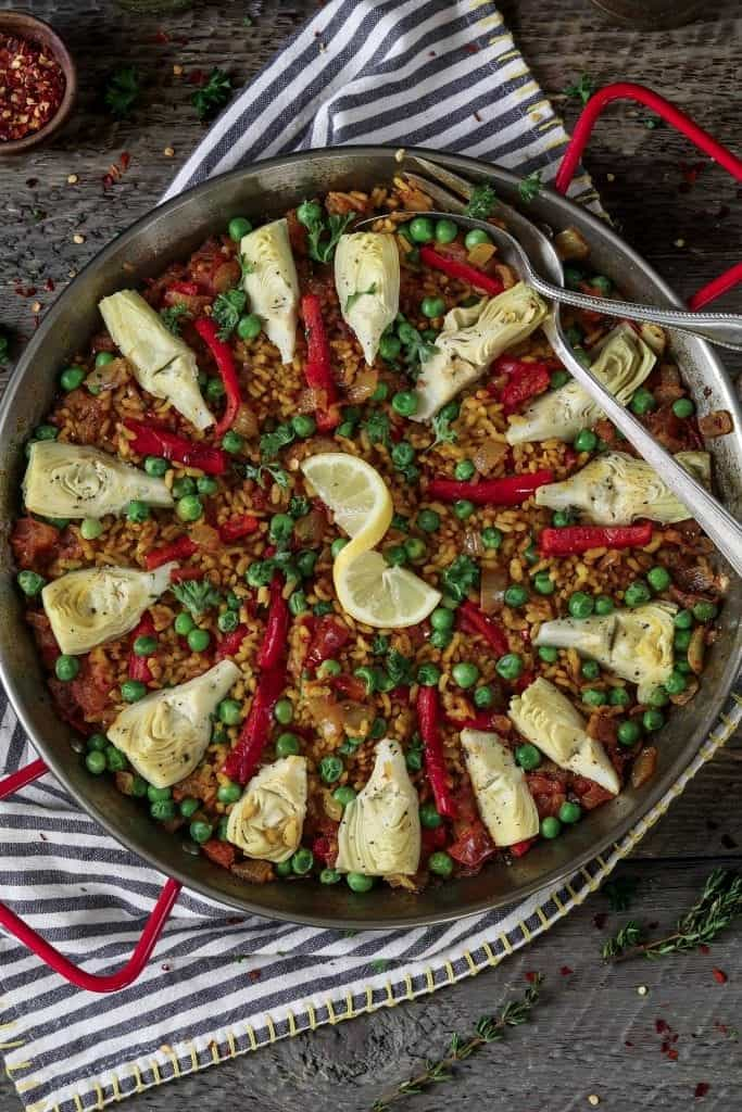 Fully cooked Vegetable Paella in a metal paella pan. Topped with artichokes, bell peppers and peas.