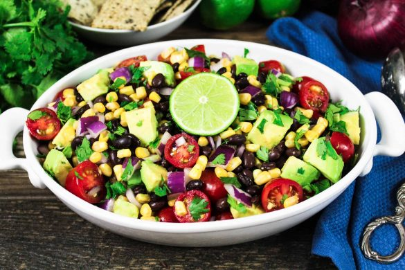 White serving bowl filled with avocado, black bean & corn salad. Topped with a slice of lime.