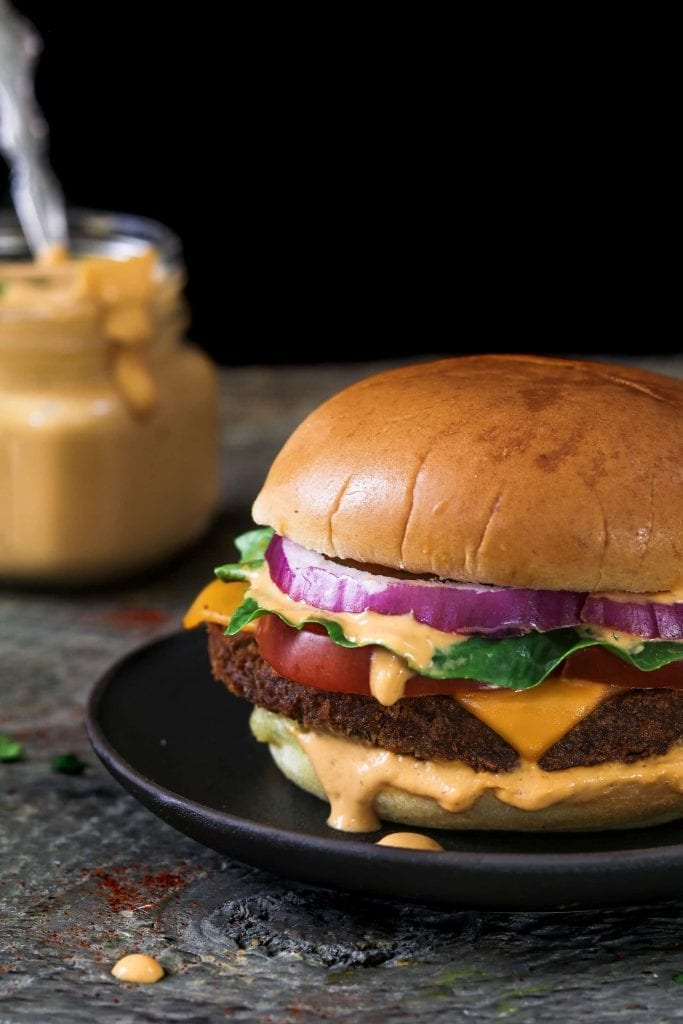 Dressed up burger with creamy chipotle sauce in the background.