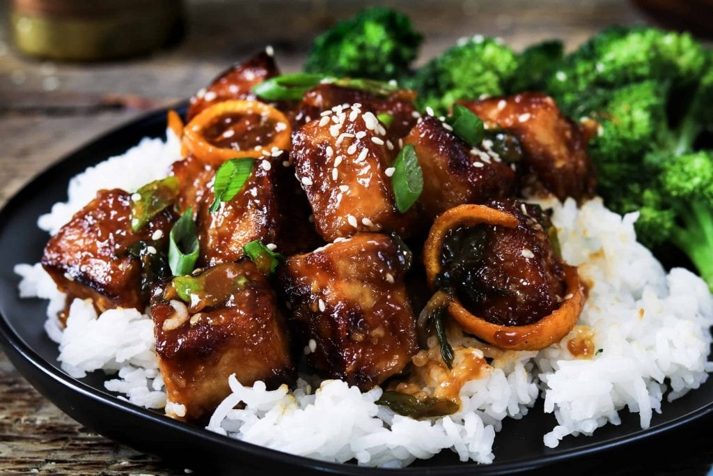 Closeup photo of General Tso's Tofu on a bed of rice with a side of broccoli.