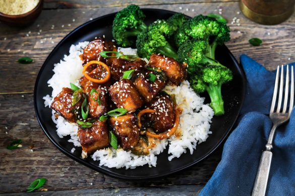 General Tso's Tofu prepared on a black plate. Side of broccoli and steamed rice.
