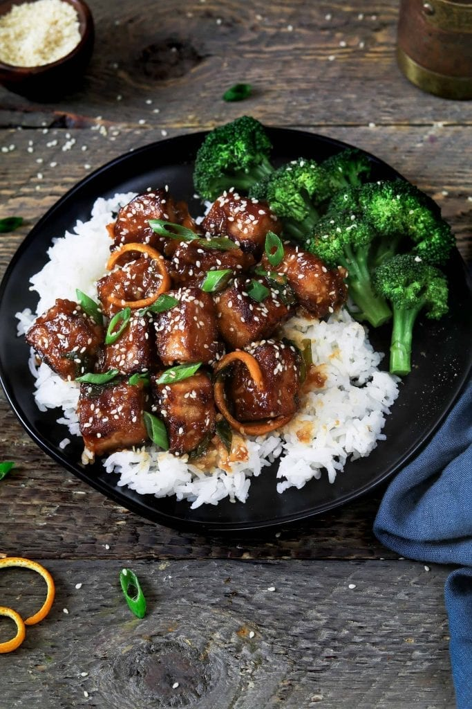 General Tso's Tofu on a black plate on top of rice. Topped with sesame seeds.