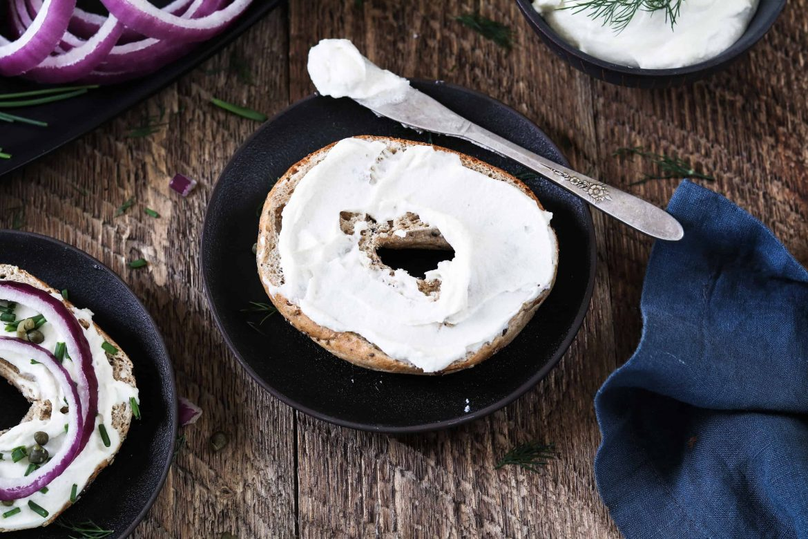 Bagel with Almond Cream Cheese on a black plate.