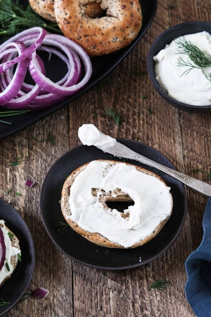 Open-faced bagel with just Almond Cream Cheese. Spreading knife on the side.