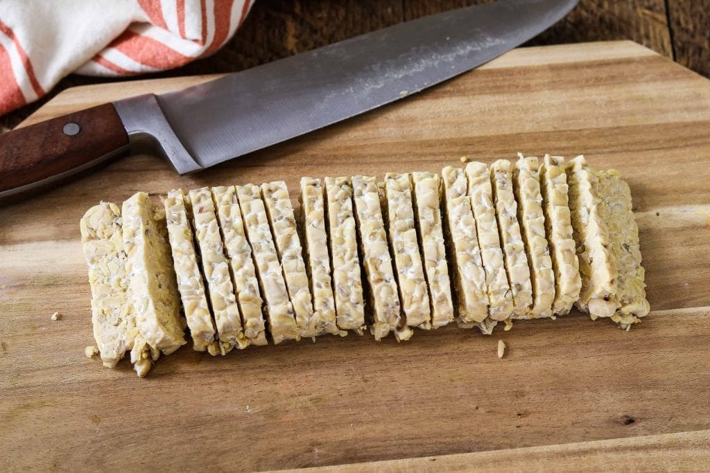 A block of tempeh cut into slices.