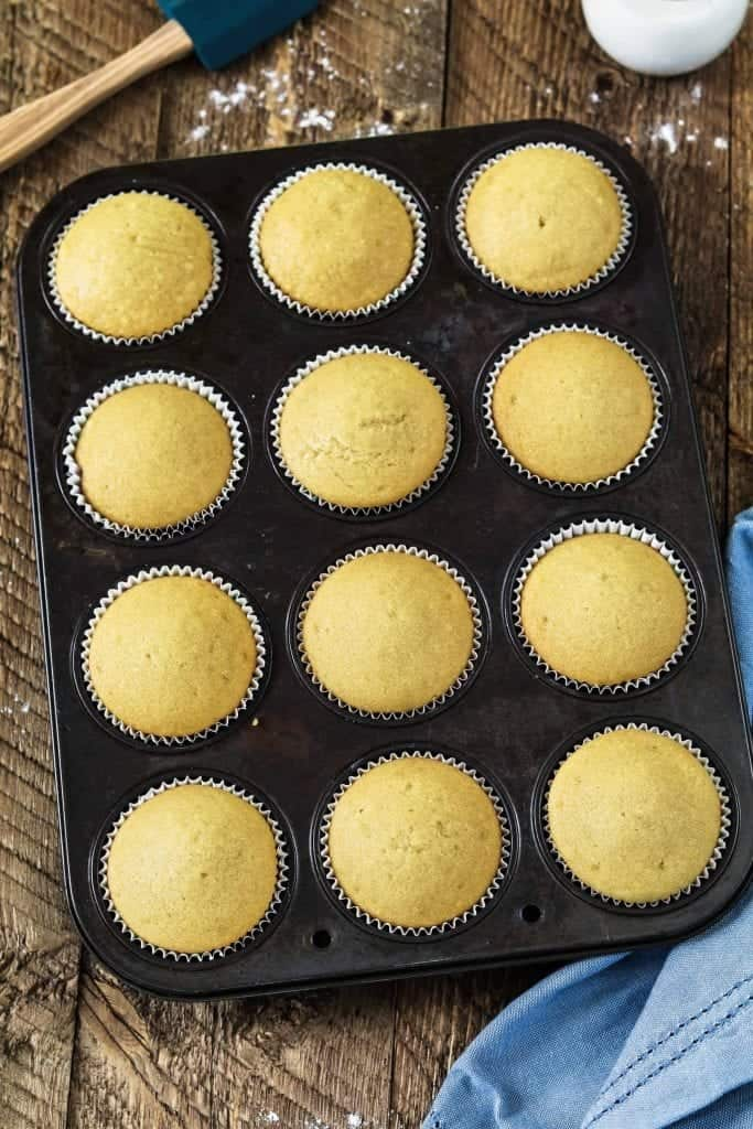 Muffin tin filled with freshly baked vegan vanilla cupcakes.