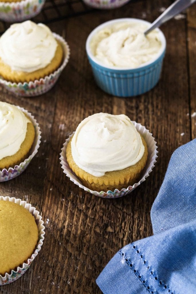 Blue ramekin with vegan cream cheese frosting. 3 frosted vegan vanilla cupcakes and one plain.