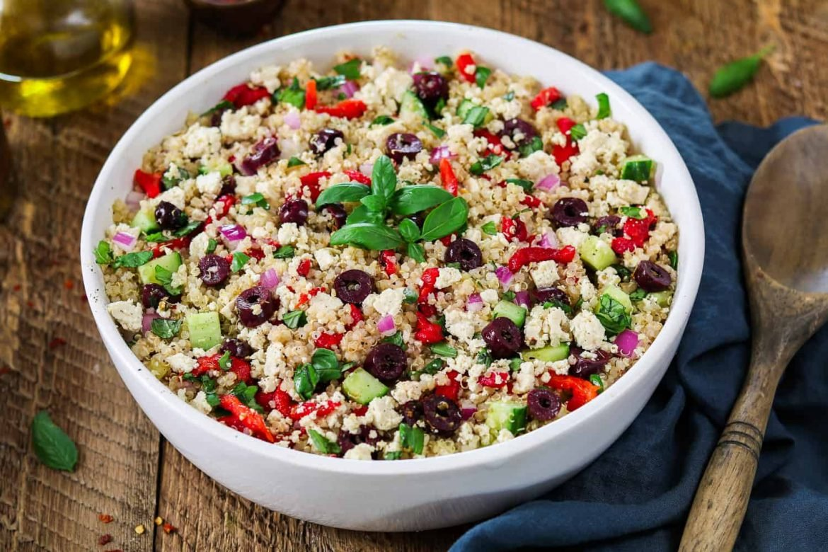 Mediterranean Quinoa Salad in a white bowl with bottle of olive oil on the side.
