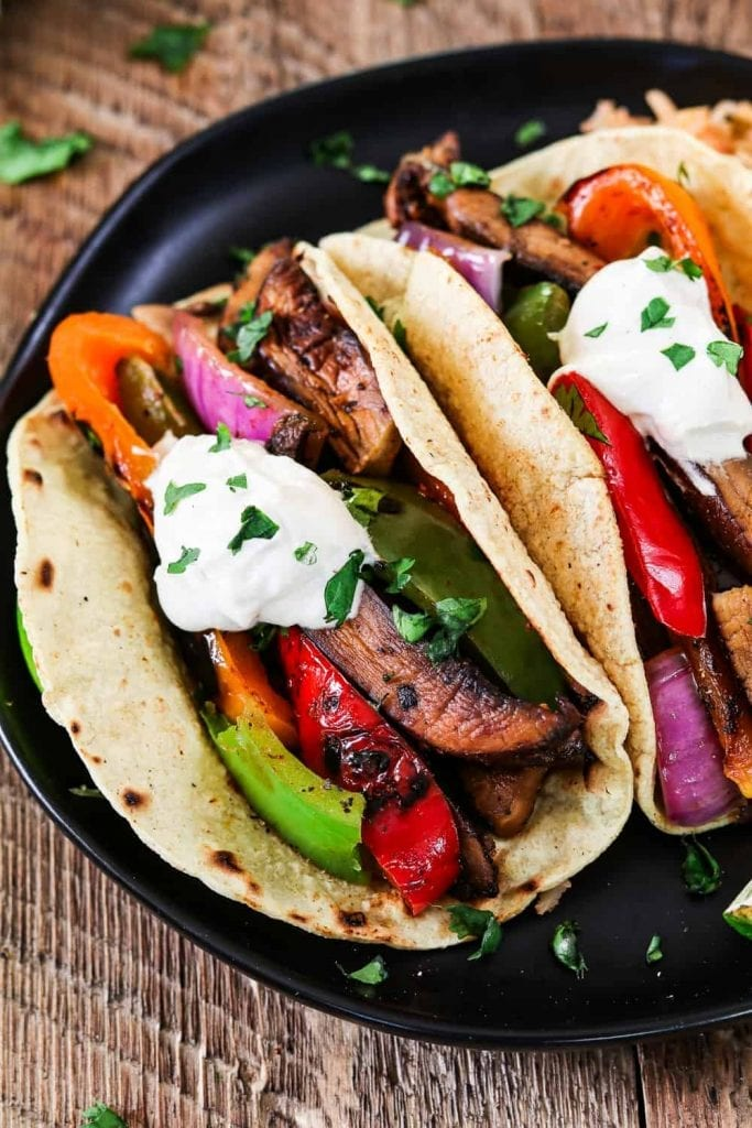closeup shot of 2 vegan fajitas, topped with vegan sour cream.