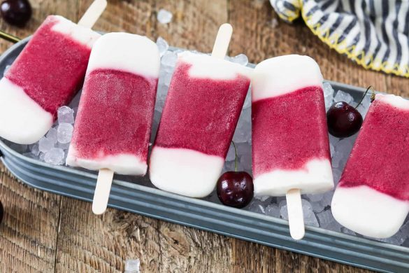 Frozen Yogurt Popsicles in a horizontal row on a bed of ice.