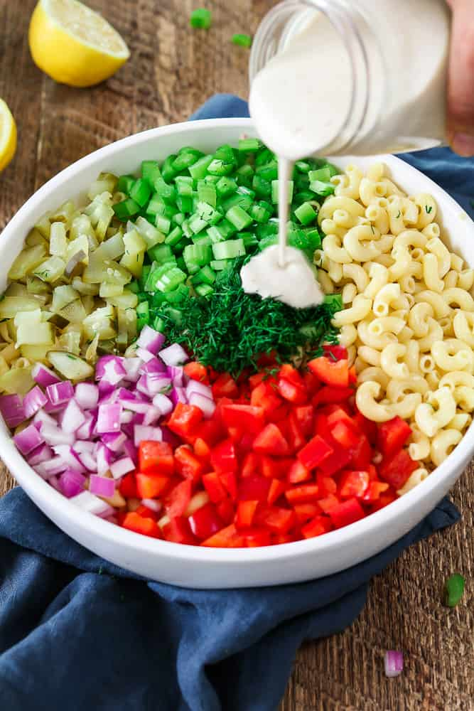 Creamy dressing pouring on top of chopped veggies in a white bowl. Vegan macaroni salad.