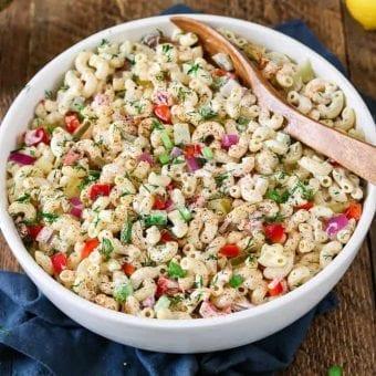 Vegan macaroni salad in a white serving bowl. Wooden bowl inside