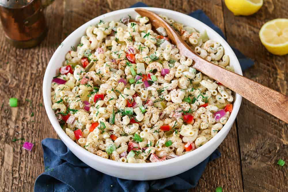 Vegan macaroni salad in a white serving bowl. Wooden bowl inside