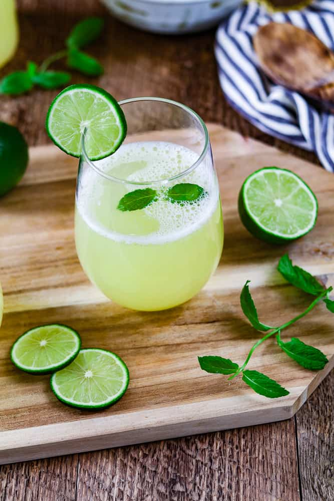 a glass of fresh limeade recipe. Fresh mint and lime wedges on the side.