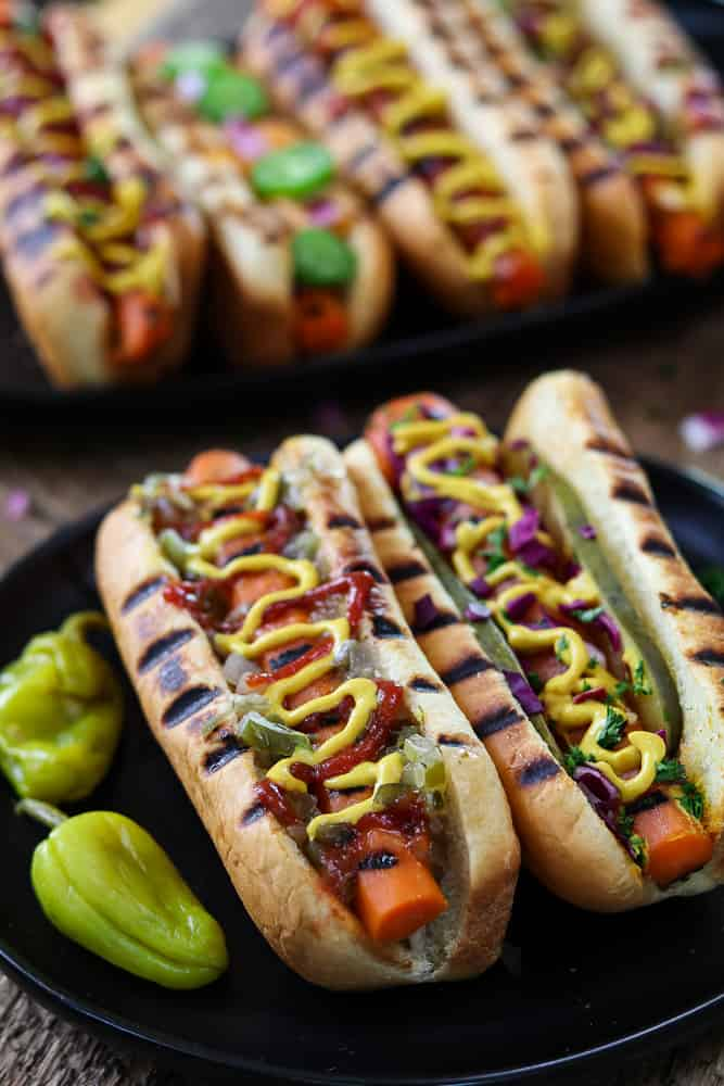 Two Vegan Carrot Hot Dogs with four in the background.