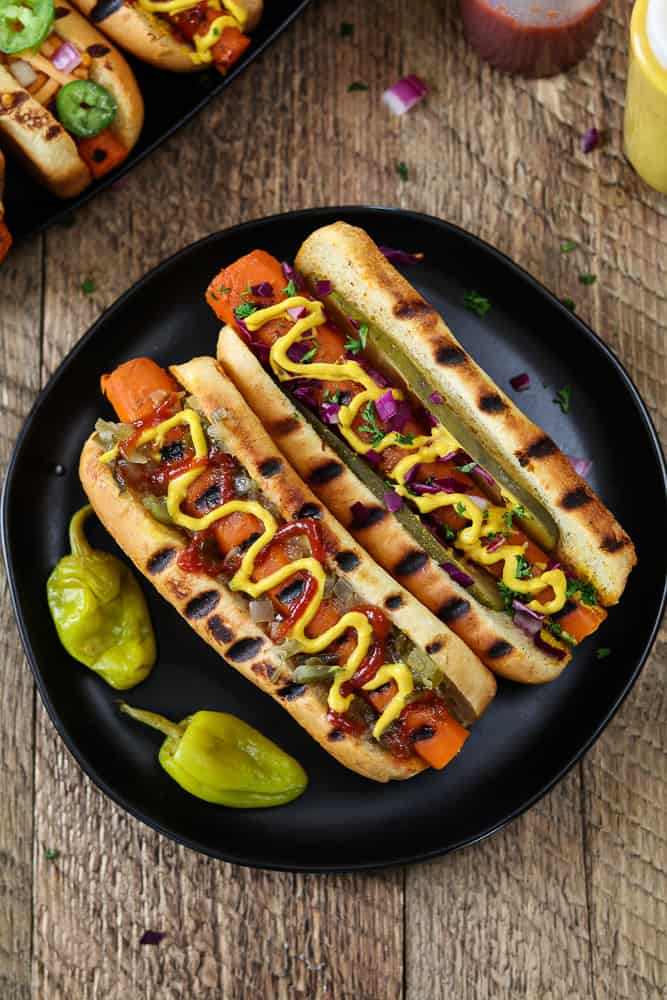 Two Vegan Carrot Hot Dogs on a black plate. Topped with mustard and ketchup.