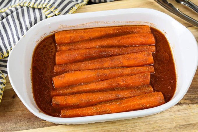 Carrots in white baking dish. Soaked in marinade.