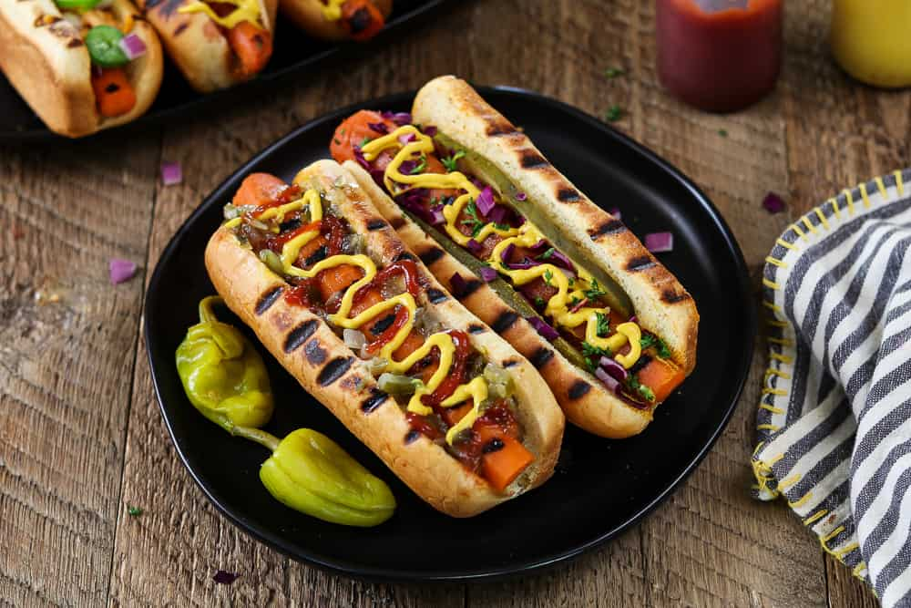 Two Vegan Carrot Hot Dogs on a plate with two pepperoncinis on the side.