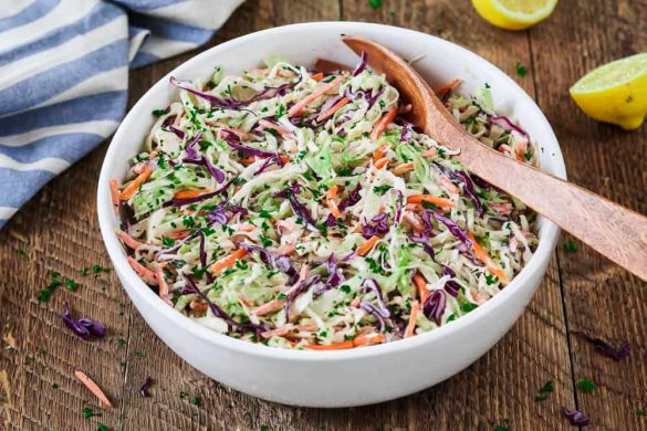 Vegan Coleslaw in a white bowl with a wooden spoon